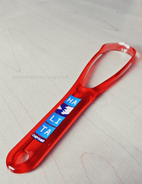 Az áttetsző piros műanyagból készülő nyelvkaparót a kék feliratkozás teszi vidámabbá.